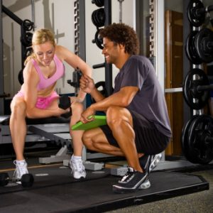 Woman doing curls with Personal Trainer