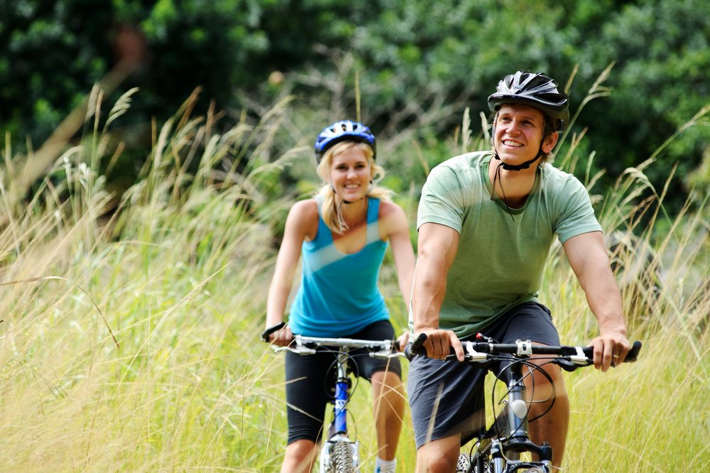 Couple cycling outdoors on country trail