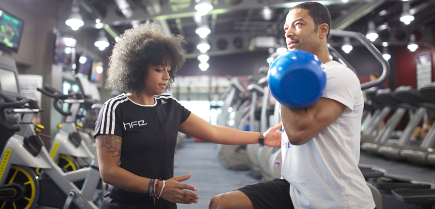 Personal trainer working with a client using a kettlebell