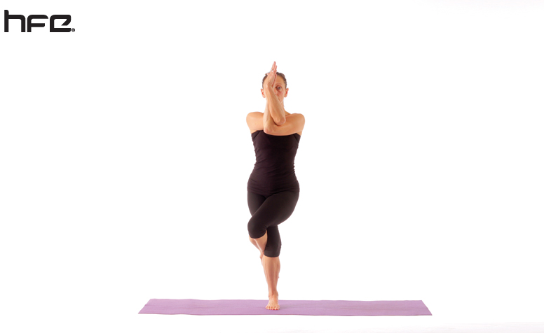 Female performing a the eagle yoga pose for low back pain