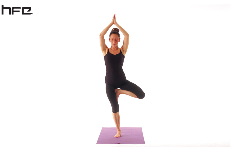 A female yoga instructor performing a tree pose