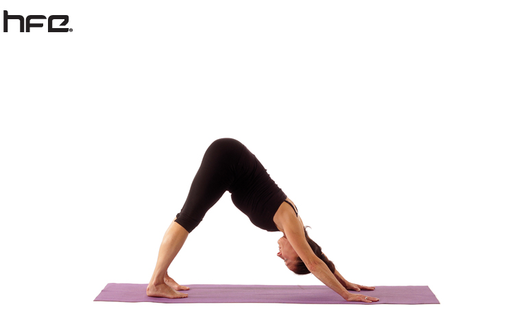 A female yoga instructor performing the downward-facing dog pose
