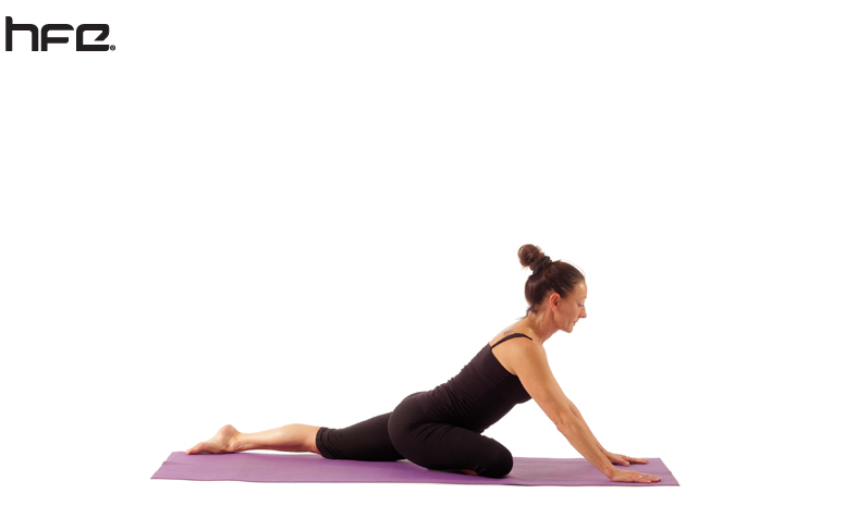 A female yoga teacher performing a pigeon pose