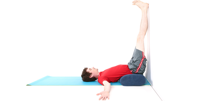 A male yoga instructor performing the legs up the wall pose