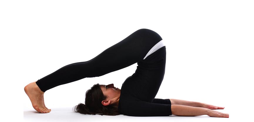A yoga teacher performing the plough pose