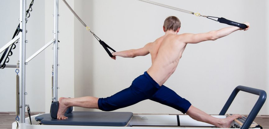 A man performing exercises on a reformer