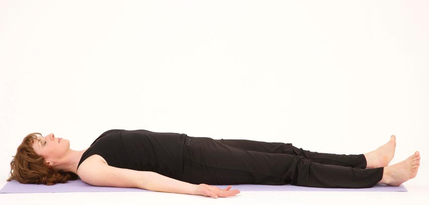 A yoga teacher performing a corpse pose