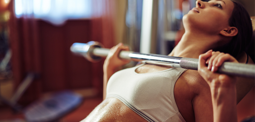 A woman preparing to lift a barbell at the gym