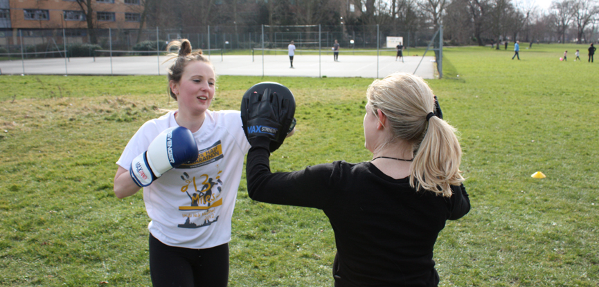 Boxing with a client at an outdoor personal training bootcamp