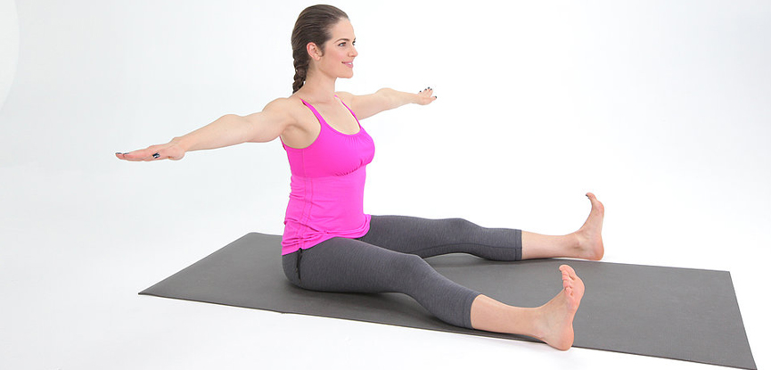 A Pilates instructor performing the Saw exercise