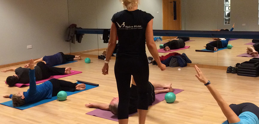 A certified Pilates instructor teaching a class