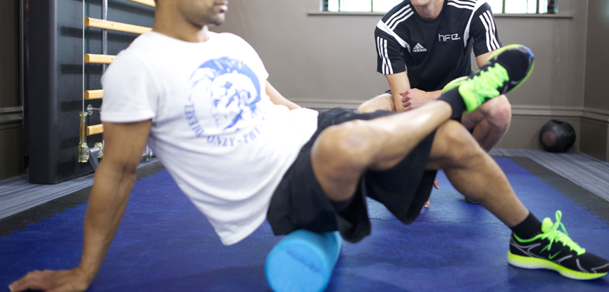 personal trainer using a foam roller