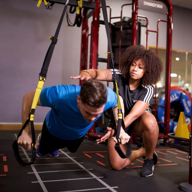 Female personal trainer working with a client on TRX straps