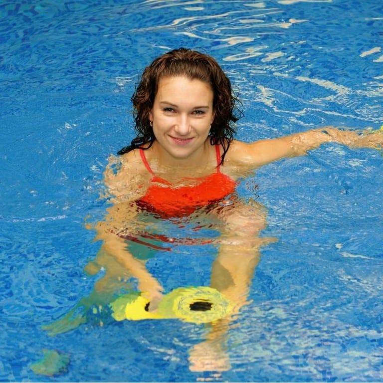 A qualified aqua aerobics instructor leading a class in the pool