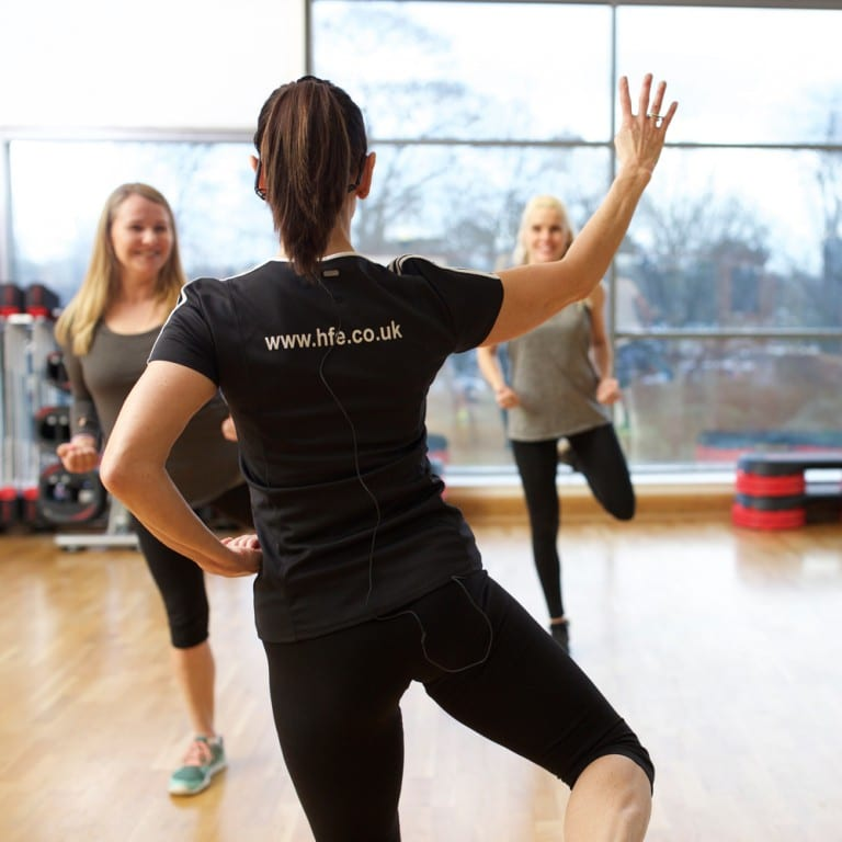 Exercise to music instructor leading a freestyle aerobics class