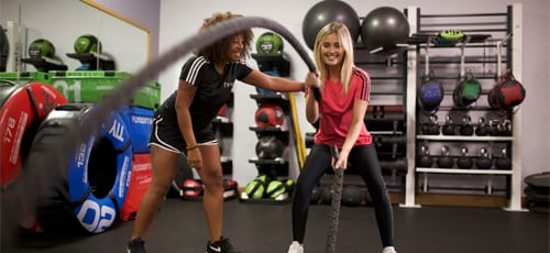 Female personal trainer assisting a client performing a battle rope exercise