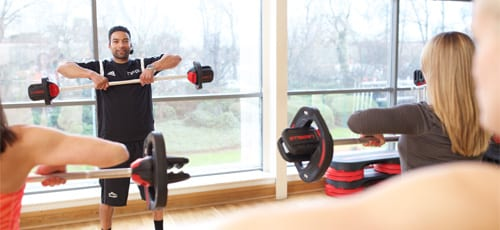 Fitness instructor using a Les Mills barbell