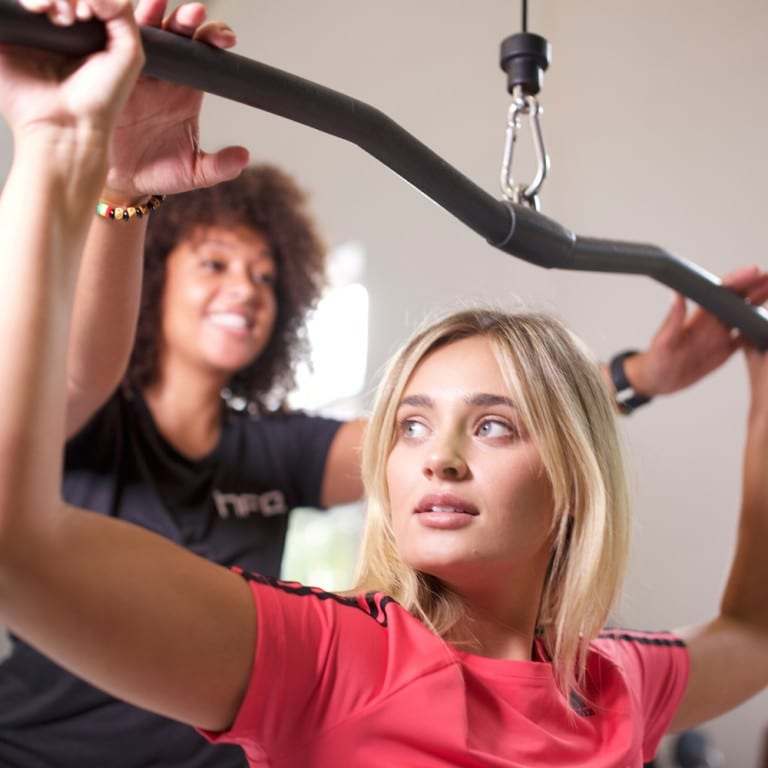 Female gym instructor assisting a client on the lat pulldown machine