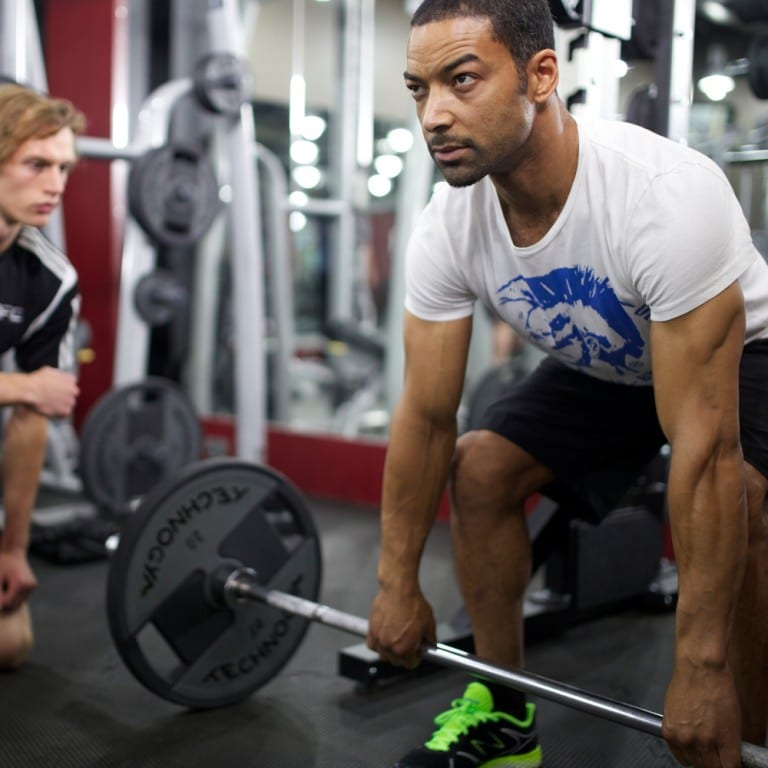 Male personal trainer assisting a client with a deadlift