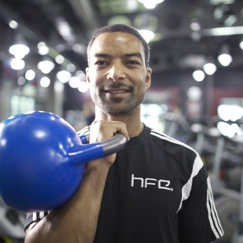 HFE personal training tutor holding a blue kettlebell