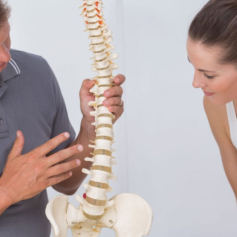 Low back spine specialist showing a patient a model of the spine