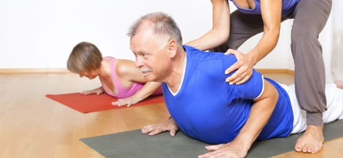 Experienced yoga teacher assisting an older man in her yoga class