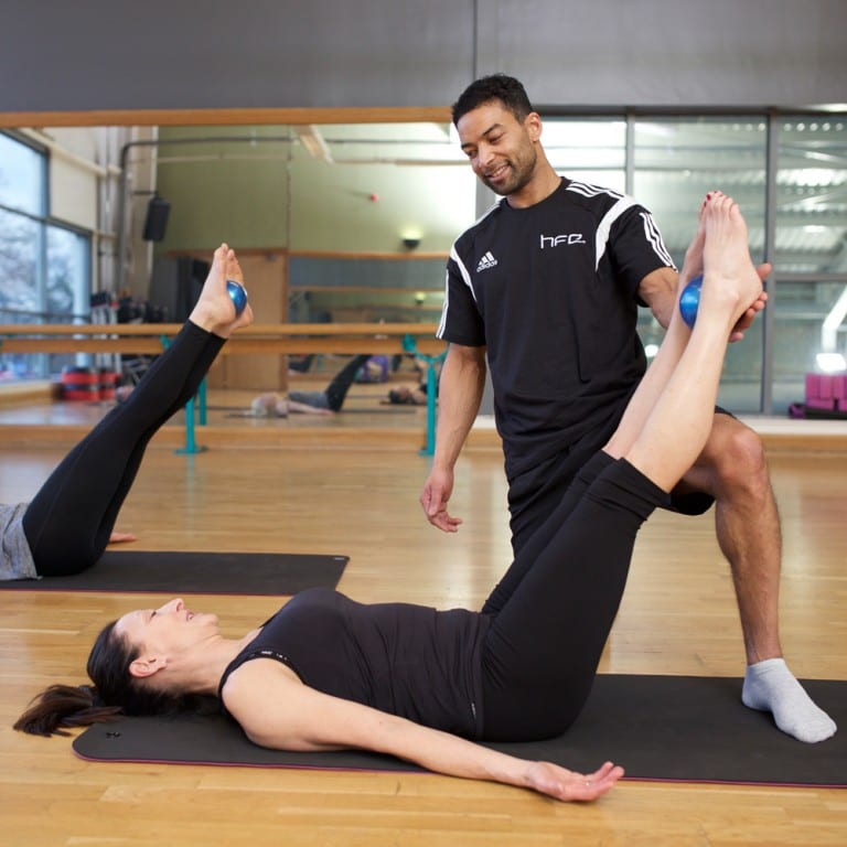 Qualified Pilates instructor assisting a client with a posture