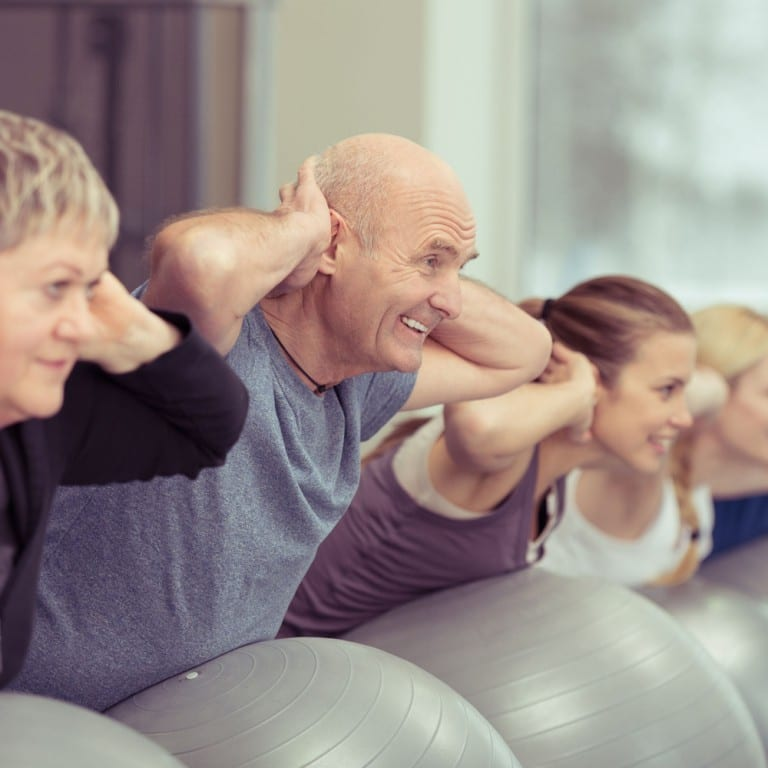 Exercise class including older adults performing exercises on a stability ball