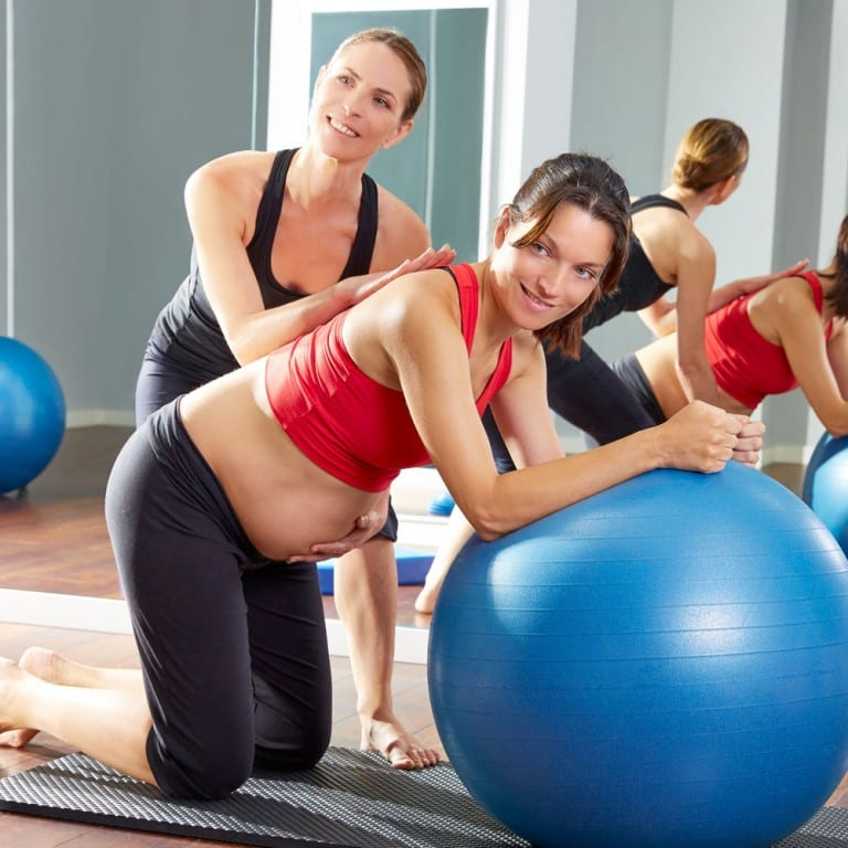 Qualified fitness instructor helping a pregnant client on a stability ball