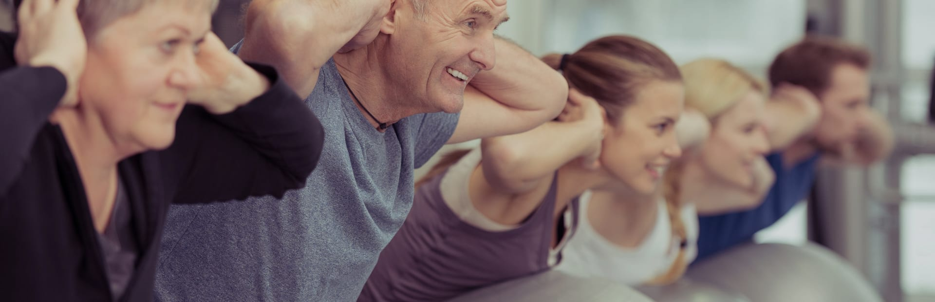 Two older adults exercising in a Pilates class