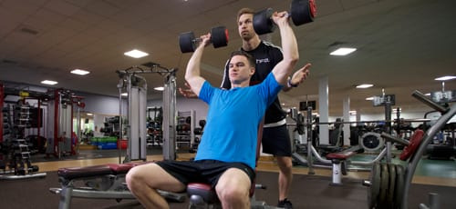 Personal trainer assisting a client with a dumbell lift
