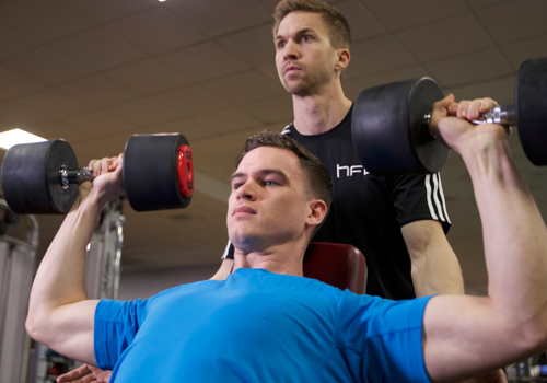 HFE tutor assisting a student a dumbbell