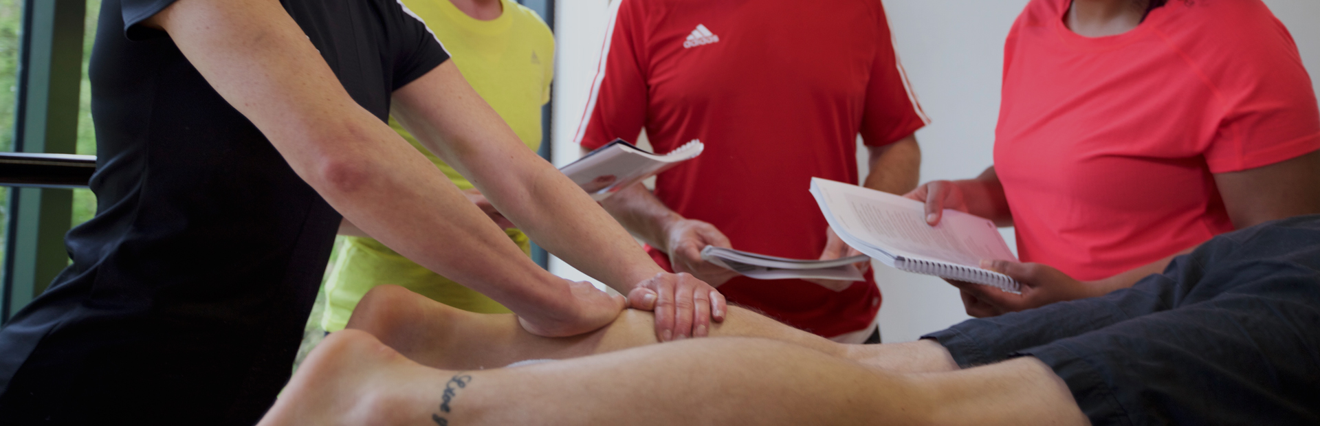 HFE tutor guiding sports massage students