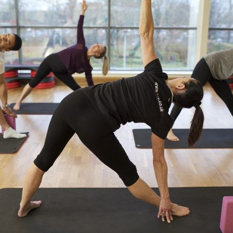HFE yoga instructor leading a class of students