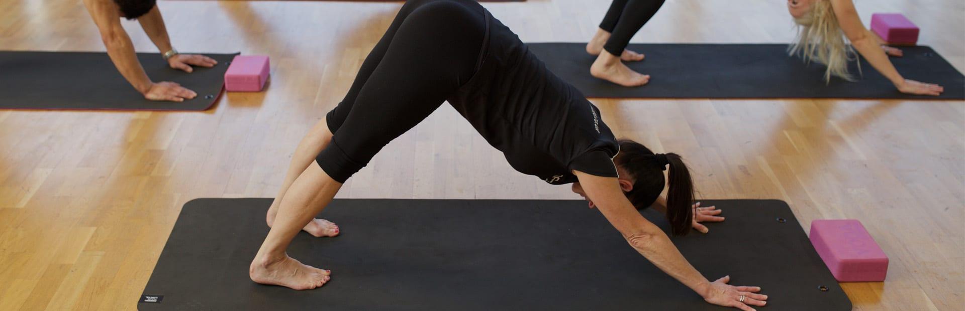HFE yoga instructor performing downward-facing dog
