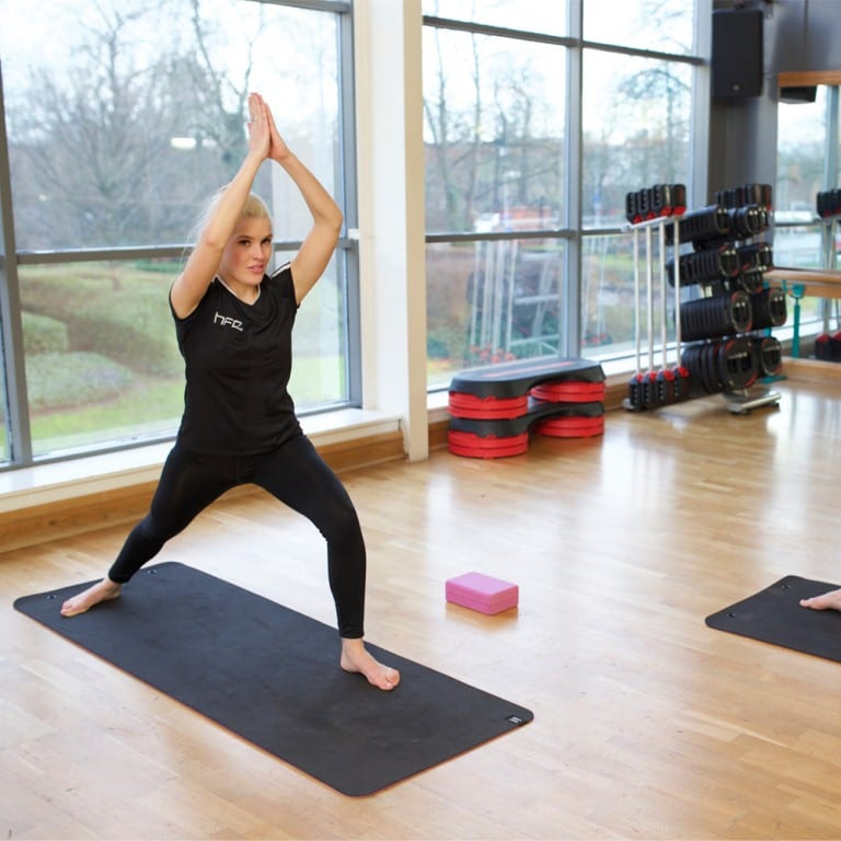 Female yoga teacher performing the Warrior 1 yoga pose in front of her class