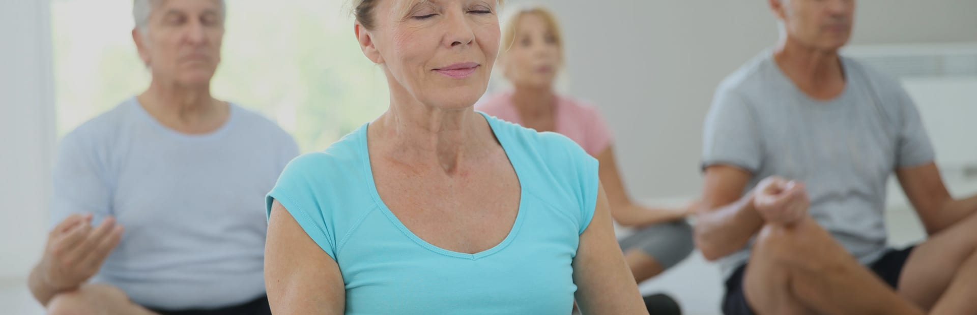 A group of older adults taking part in a yoga class