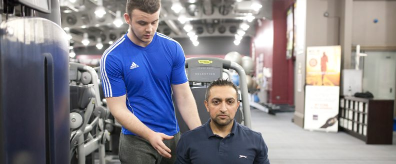 Gym instructor assisting a member