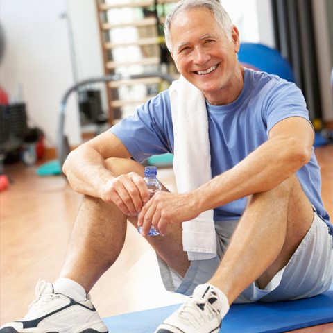 Older adult sitting in an exercise studio post workout