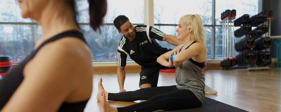 Qualified Pilates instructor assisting an exerciser