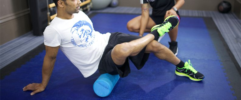 A sports therapist using a foam roller with a client