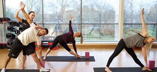 Yoga class performing Trikonasana or triangle pose