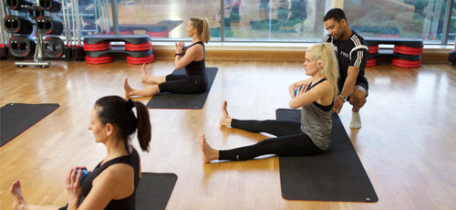 Pilates instructor helping a participant with correct alignment