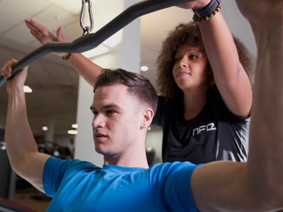 Personal trainer working with a client on a lat pull down machine