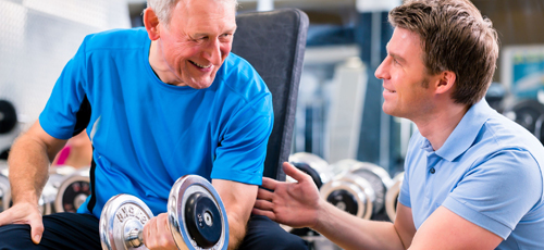 Exercise referral instructor working with an older man in the gym