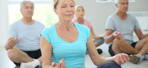 Older adults taking part in relaxation after a yoga class