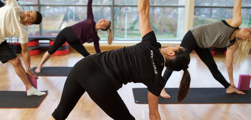A yoga class performing the triangle pose