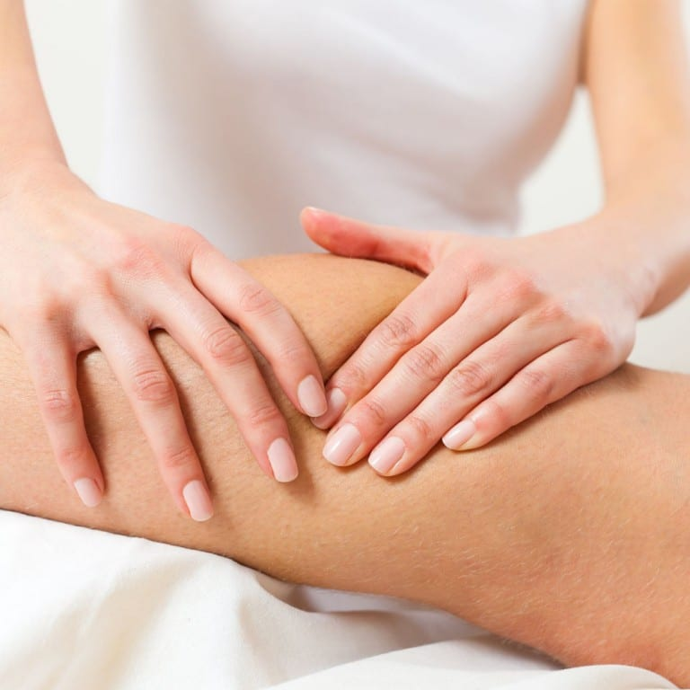 Sports massage therapist working a client's knee