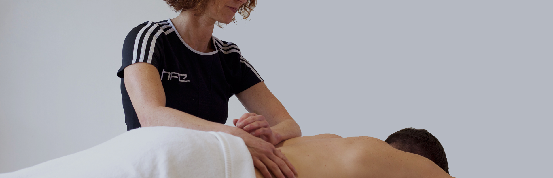 Qualified massage therapist working with a client on HFE's sport massage courses