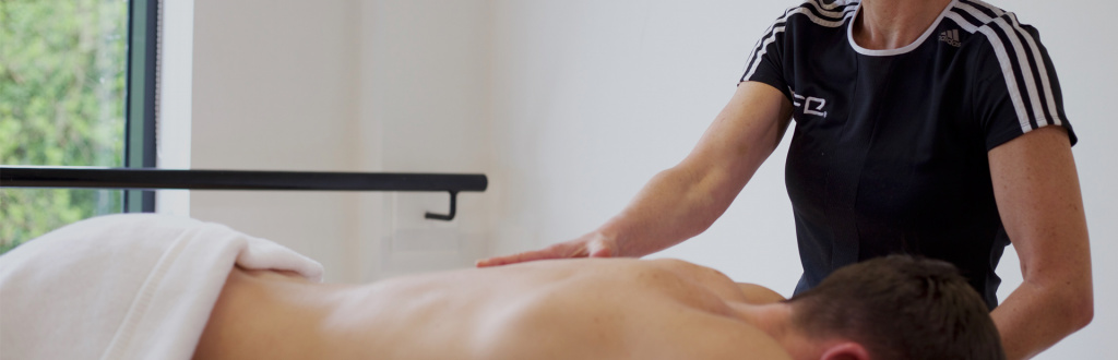 Qualified sports massage therapist working on a client's back